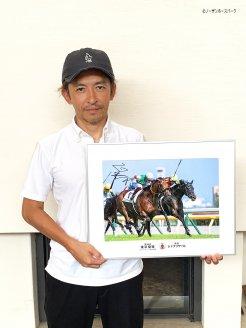 福永騎手は、サイン入りのシャフリヤールの日本ダービー優勝写真パネルを提供